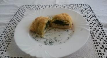 Zdjęcie przedstawia faszerowana pierś kurczaka w cieście francuskim na talerzu