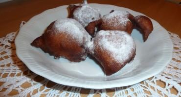 Pączki z serka homogenizowanego posypane cukrem pudrem na białym talerzyku