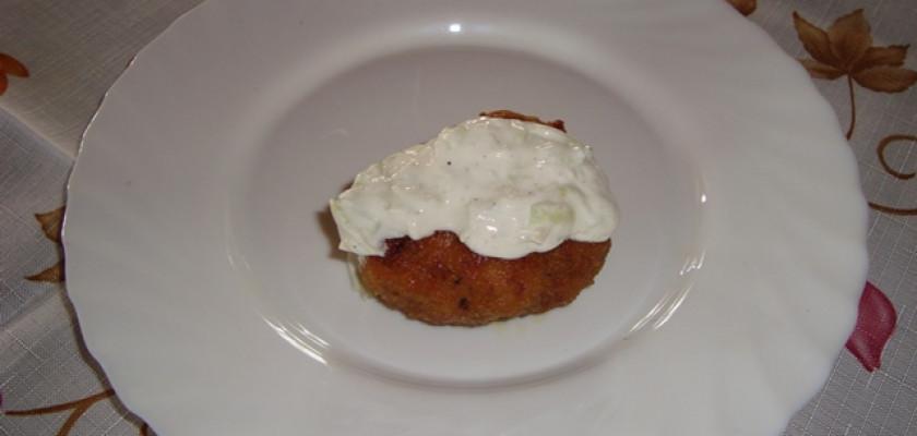 Zdjęcie przedstawia pieczony kotlecik mielony w stylu greckim na talerzyku