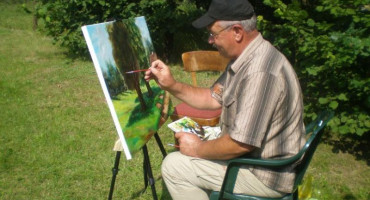 Zdjęcie przedstawia Pana Jerzego Kacprowskiego podczas malowania obrazu na łonie natury