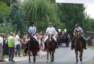trzy konie jadące z ludźmi oraz bryczka zaciągnięta w konie jadąca z tyłu