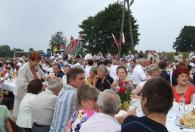 ludzie siedzący prz zastawionych stołach pod gołym niebem