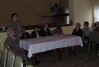 grupa ludzi przy stole przykrytym białym obrusem
