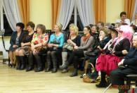 grupa kobiet siedząca na krzesłach pod sceną