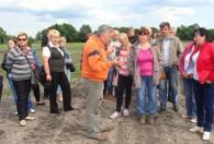 grupa ludzi na polu słuchająca mężczyzny w pomarańczowej bluzie