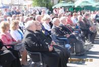 grupa ludzi siedząca na krzesłach pod sceną na dożynkach