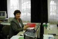 kobieta w siwej marynarce siedzi przy biurku